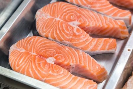 shopwindow: raw salmon steaks on metal box in shop-window