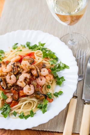 pasta with seafoods and white wine on napkins photo
