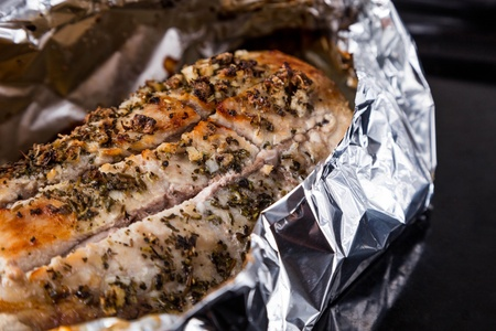 cook griddle: baked pork meat with seasoning in foil on black tray