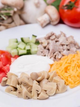 салата из нарезанных овощей, мяса и шампиньонов с гарниром на белой тарелке Фото со стока