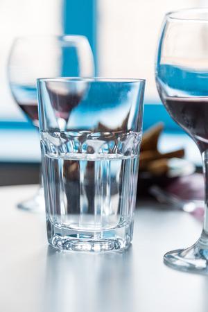 стекло с водой и бокалами с красного на синем фоне окна Фото со стока