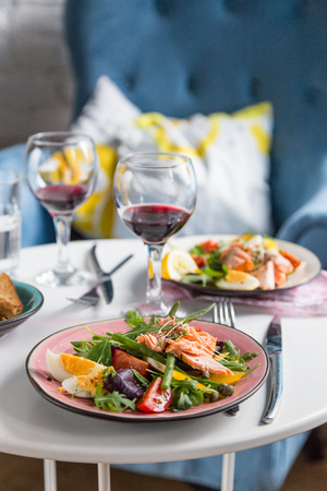 salad with salmon and verdure in pink plate on table with blue chair background photo