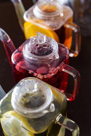 three square teapots with different colors fruit tastes of tea photo