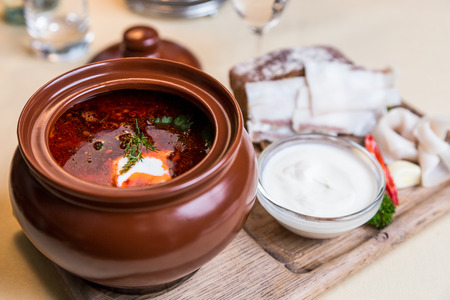 metall and glass: Restourant serving dish - soup on wooden board on table Stock Photo