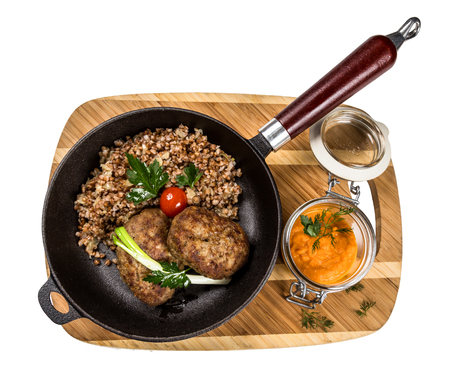 metall and glass: cutlet with buckwheat on wooden board on white background