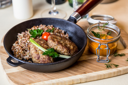 metall and glass: cutlet with buckwheat on wooden board