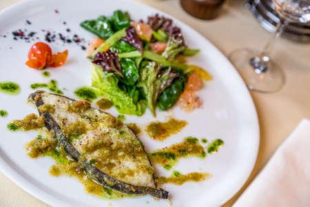 metall and glass: roast slice fish on table