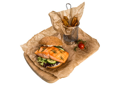 metall and glass: burger with salmon, frying potato on wooden board