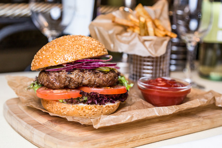 metall and glass: burger with cutlet with frying potato on wooden board