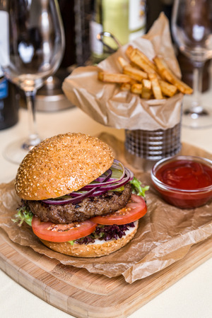 burger with cutlet with frying potato on wooden board