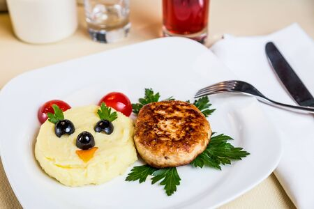 metall and glass: Restourant serving dish for child`s menu - potato puree, cutlet with face on white background