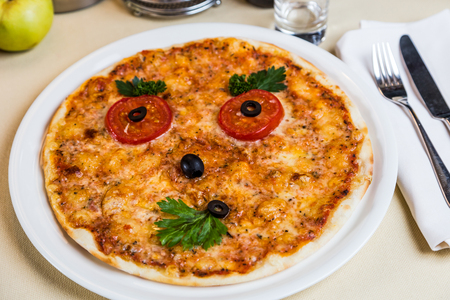 metall and glass: Restourant serving dish for child`s menu - pizza with face Stock Photo