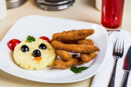 metall and glass: Restourant serving dish for child`s menu - potato puree, stick with face Stock Photo
