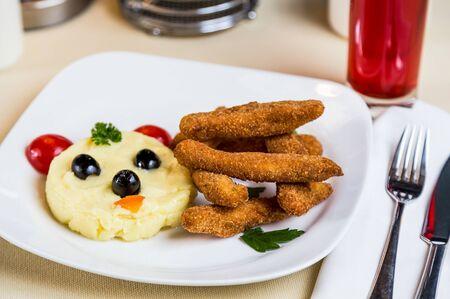 Restourant serving dish for child`s menu - potato puree, stick with face Stock Photo