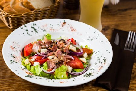 meat salad with spices and vegetables with light beer on on wooden table