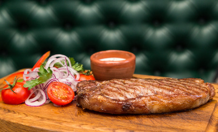 green sofa: roast meat steak with vegetable garnish and sauce on wooden board with background green sofa