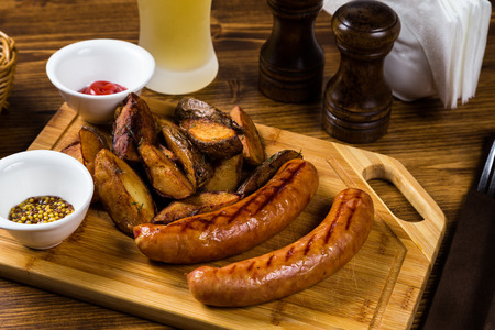 Grilled sausages with roast potato with spices on wooden board with light beer on table Stock Photo