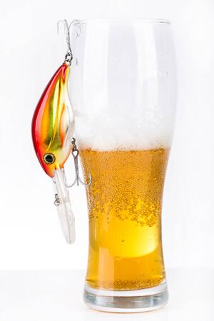 near beer: closeup fishing bait wobblers near glass with light beer