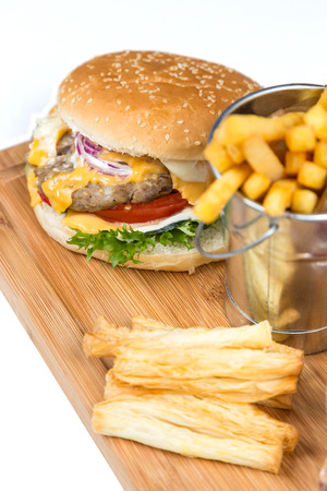 classic burger: burger with fried potatos in bucket serving on wooden board Stock Photo