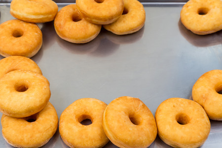 portly: fried equal round doughnuts in frame on metal tray Stock Photo