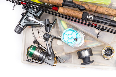 different fishing tackles - rod, reel, line and lures in box on white background Stockfoto