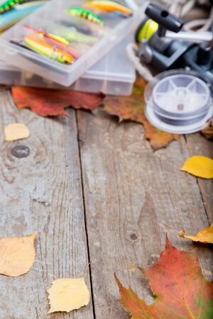lead rope: fishing tackles wobblers and lures in box on wooden board with leafs of autumn