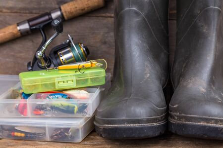 fishing catches: fishing tackles rod, reel, wobblers in boxes with rubber boots on timber board background. for design advertising or publication