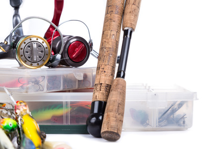 overturn: fishing tackles, fishing lure and fishing bait on plastic storage boxes on bright white background. for design advertising or publication Stock Photo