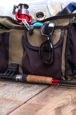scheide: fishing tackles and lures in open handbag on wooden background. for design advertising or publication Lizenzfreie Bilder
