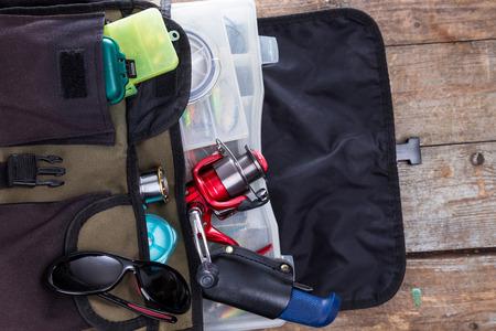 schwertscheide: Angelger�te und K�der in der offenen Handtasche auf Holz-Hintergrund. f�r die Gestaltung der Werbung oder die Ver�ffentlichung