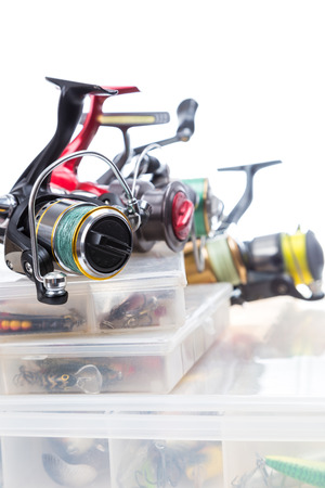 baits: different fishing reels on storage boxes with fishing baits and lures