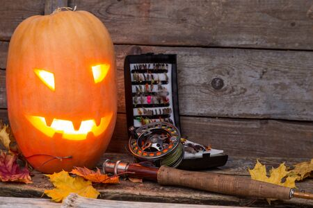 flyfishing: halloween pumpkin head with fly-fishing tackles on wooden boards background