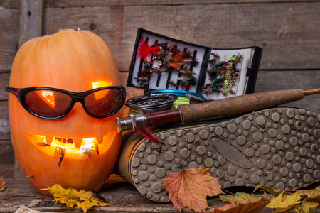 wading: halloween pumpkin head with wading boots and fly-fishing tackles on wooden boards background