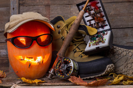 flyfishing: halloween pumpkin head with wading boots and fly-fishing tackles on wooden boards background