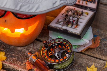 flyfishing: halloween pumpkin head in hat with fly-fishing tackles on wooden boards background Stock Photo