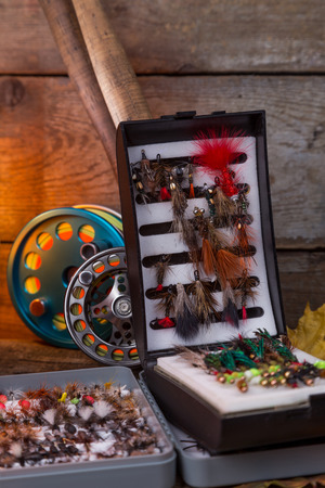 flyfishing: fly-fishing tackles on wooden boards background