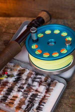 fly-fishing tackles on wooden boards background