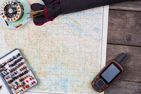 intend: intend to fishing journey with fly-fishing tackles and gps navigator on paper map background Stock Photo