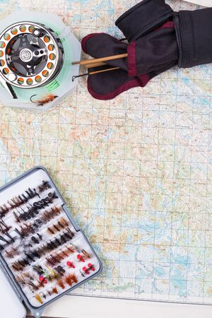 intend: intend to fishing journey with fly-fishing tackles on paper map background