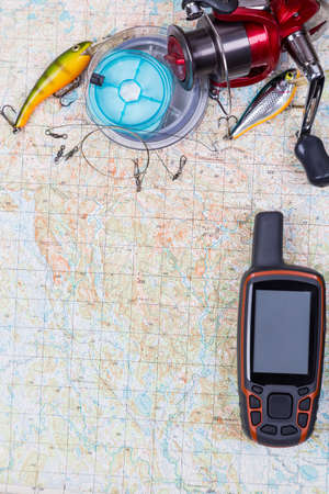 rout: preparation in fishing journey with fishing tackles and gps navigator on map background