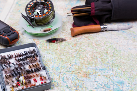 intend: intend to fishing journey with fishing tackles and gps navigator on paper map background Stock Photo