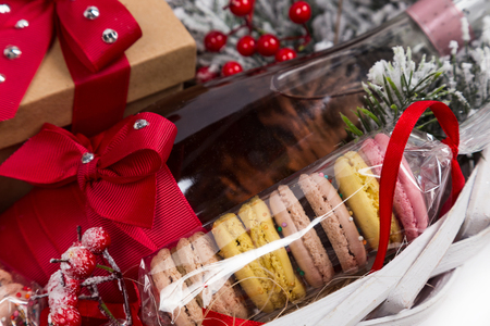 christmas drink: christmas present in basket with sweet pastry, bottle of wine and decor
