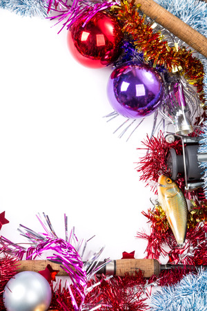 christmas and new year frame for fishers and anglers. fishing tackles on bright spangles and ball background Stock Photo