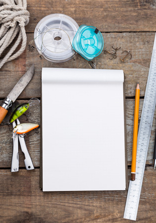 lead rope: white writing-book with fishing tackles and design tools on wooden board. for mockup, print, design.