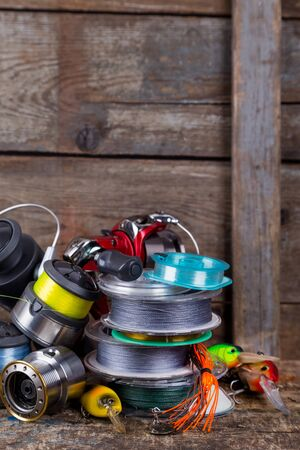 sport fishing tackles, baits, reels, spool with line on background of wooden timbers Stock Photo