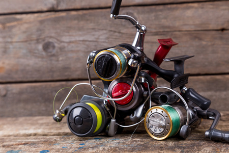 original idea: heap different fishing reels with line on wooden background. color tackles with original idea for design Stock Photo