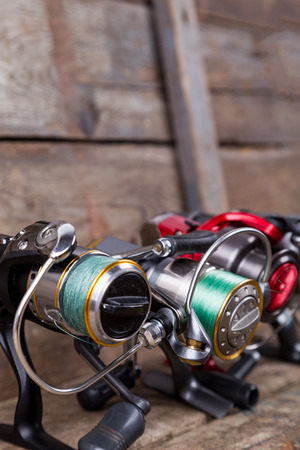 heap different fishing reels with line on wooden background. color tackles with original idea for design Stock Photo