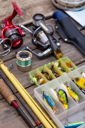 clasp knife: different fishing tackles for journey on background of wooden boards