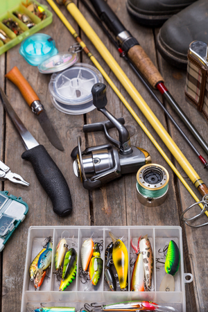 tackles: different fishing tackles for journey on background of wooden boards