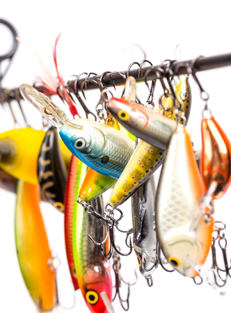 suspended: closeup different bright colored fishing bait wobblers be suspended on rod`s blank with white background